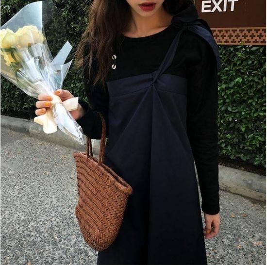 ワンショルダージャンパースカートを着た女性