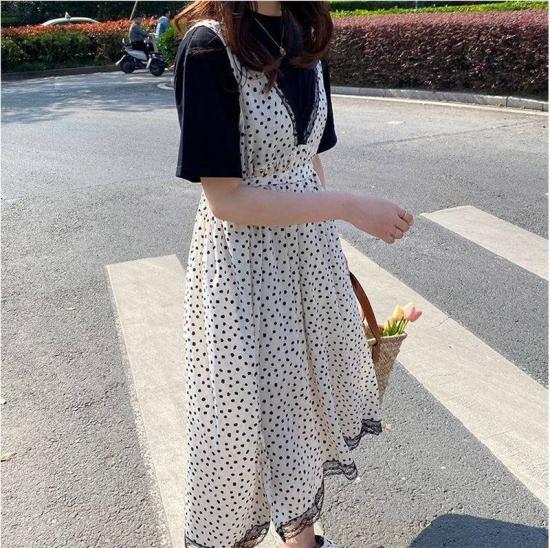 ドット柄ジャンパースカートを着た女性